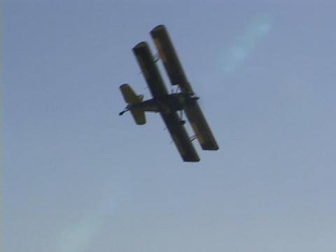 A crop duster flies over farm fields Stock Video Footage