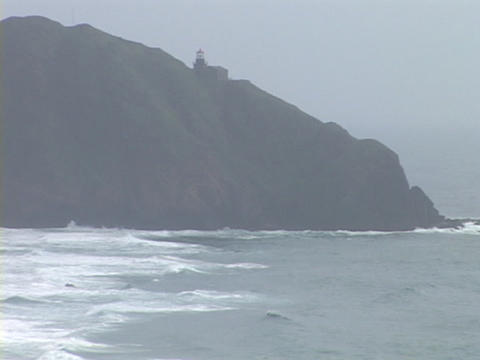 A distant lighthouse shines in the fog atop a rocky... Stock Video Footage