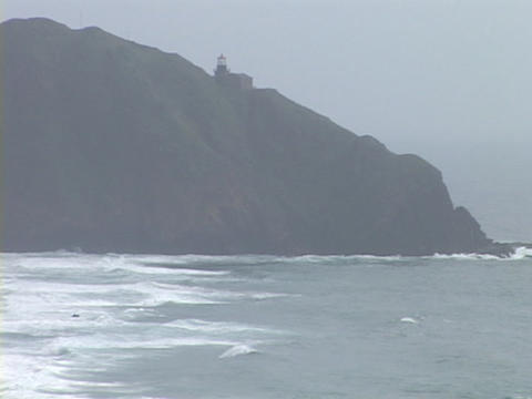 A distant lighthouse shines in the fog atop a rocky coastline Footage