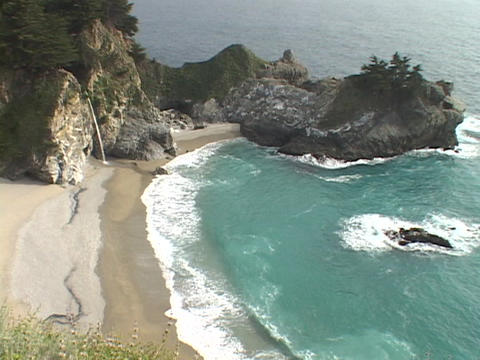 A gentle waterfall spills onto the sandy shore along the rugged Big Sur coastline Footage