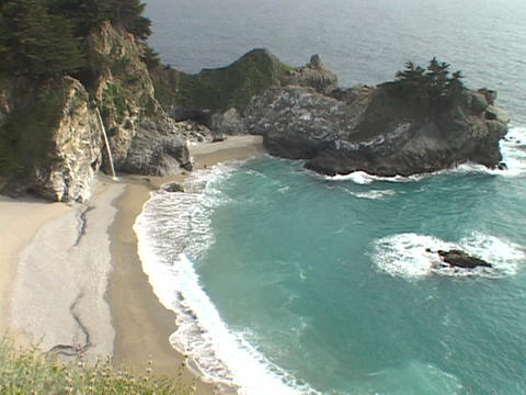 A gentle waterfall spills onto the sandy shore along the... Stock Video Footage