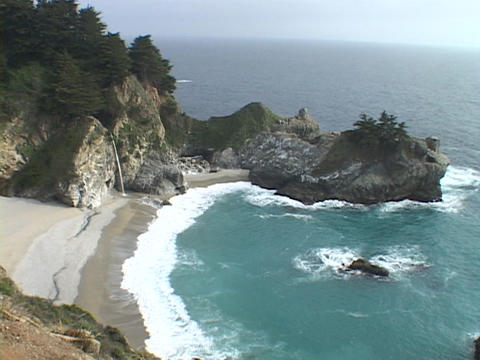A waterfall spills onto the sandy beach in Big Sur Stock Video Footage