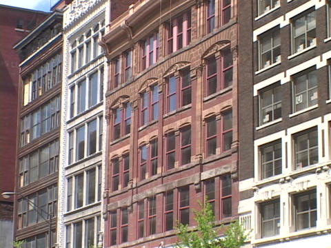 Windows cover the front of a row of brownstone buildings Footage