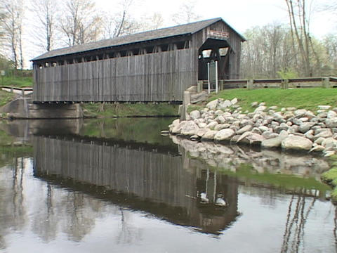 A covered bridge reflects in a Madison County river Stock Video Footage