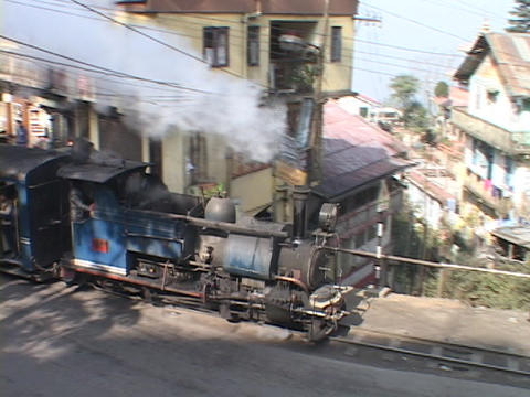 A steam train passes the city of Darjeeling, India Stock Video Footage