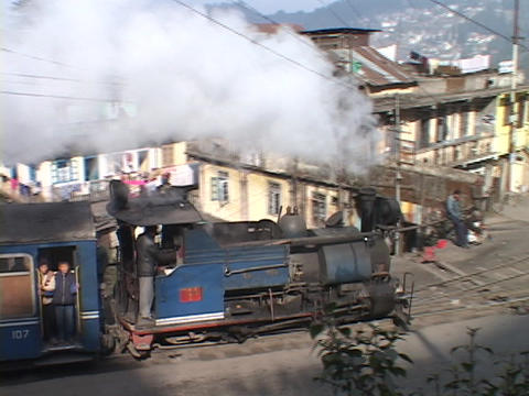A steam train passes the city of Darjeeling, India Footage