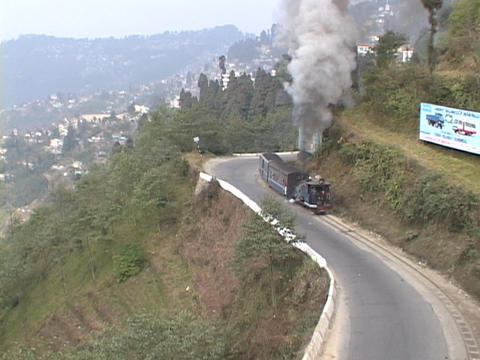 Steam train winds through the mountains near Darjeeling, India Footage