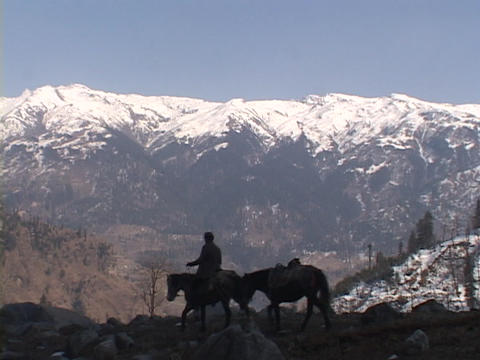 A man rides his horse across a rocky field Stock Video Footage