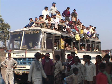 Passengers sit atop a crowded bus Footage