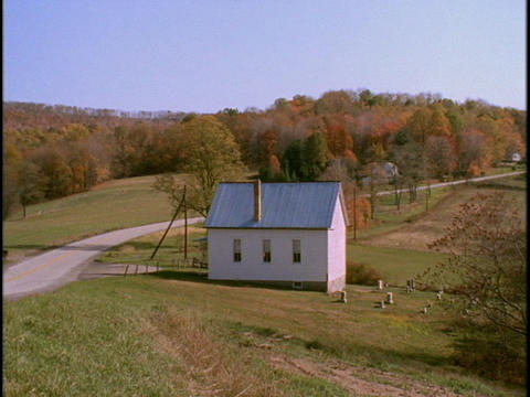 A country road winds beside a farmhouse Footage