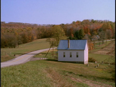 A country road winds beside a farmhouse Stock Video Footage