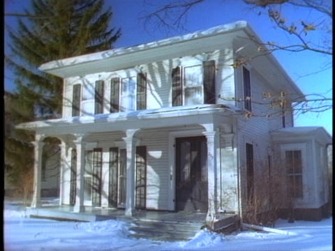 Snow covers the ground in front of an old house Stock Video Footage