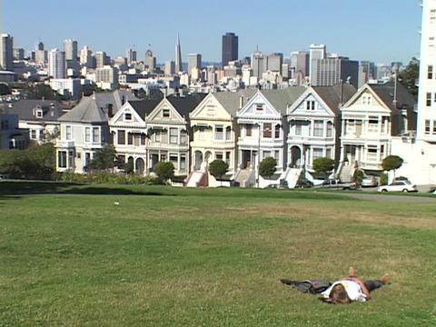 A man lounges on the grass in a Victorian neighborhood in San Francisco, California Footage