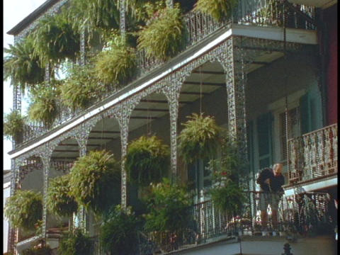 A man sweeps a balcony in New Orleans Stock Video Footage