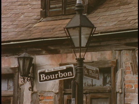 A Bourbon street sign hangs on a lamppost Stock Video Footage
