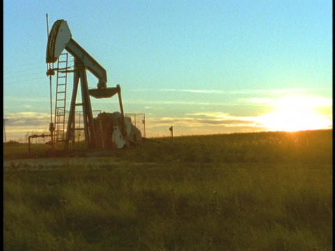 An oil derrick pumps oil Stock Video Footage