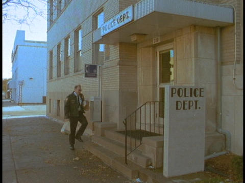 An officer walks into a police station Stock Video Footage