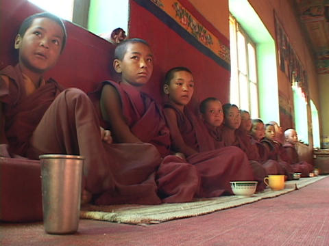 Buddhist boys at a monastery sit in a long row Stock Video Footage