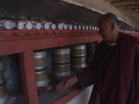A Buddhist monk spins prayer wheels Stock Video Footage