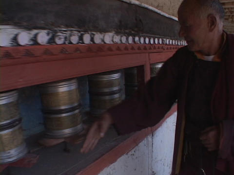 A Buddhist monk spins prayer wheels Live Action