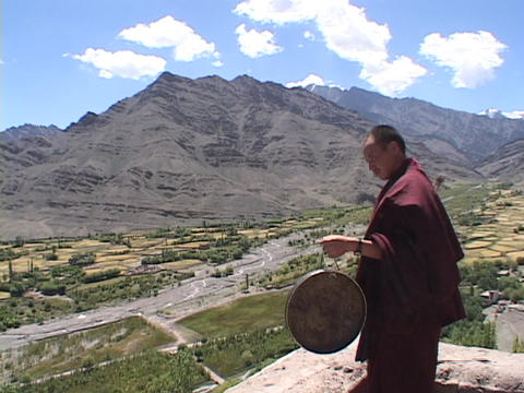 A Buddhist monk strikes a gong Live Action