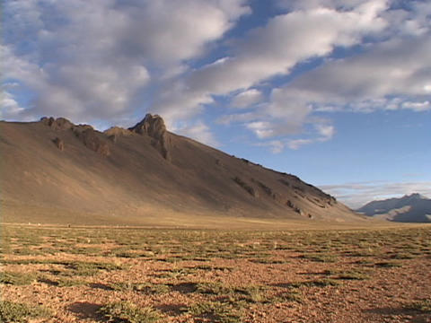 Clouds cast shadows on hills and a desert Footage