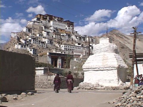 Tourists wander through a village beneath a monastery in... Stock Video Footage