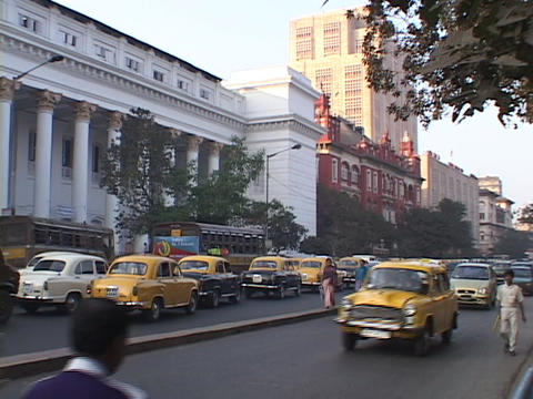 Traffic drives down a busy street in Calcutta, India Footage