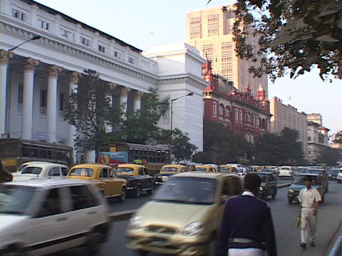 Traffic drives down a busy street in Calcutta, India Stock Video Footage