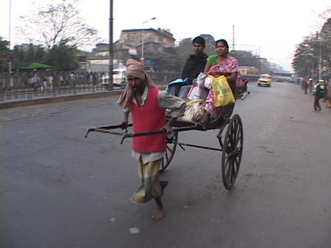 A man pulls a rickshaw on the streets of Calcutta, India Stock Video Footage