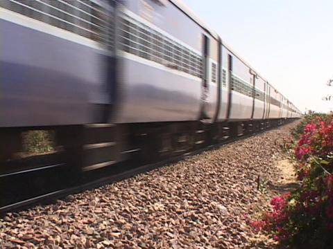 A passenger train moves along the train tracks Footage