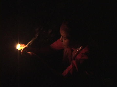 A Hindu woman prays by candlelight Stock Video Footage