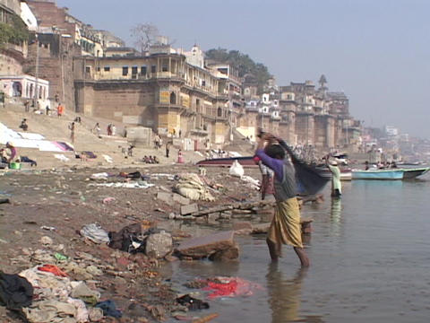 People wash clothes beside the Ganges River in Varanasi,... Stock Video Footage
