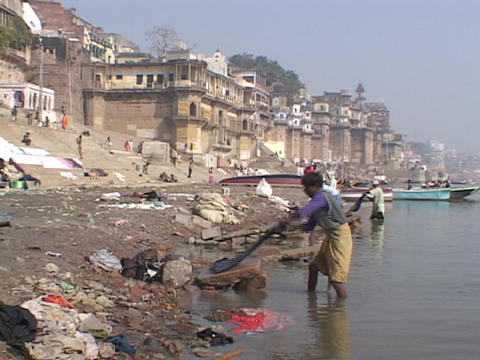 People wash clothes beside the Ganges River in Varanasi, India Footage