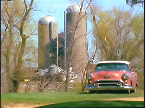 Grain silos rise above an old car Live Action