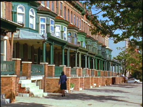 A pedestrian walks by row houses Live Action
