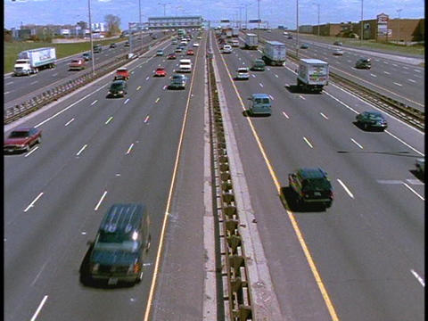 Cars and trucks drive along a busy freeway Footage