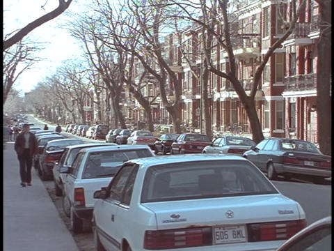 Cars line the streets in front on apartment buildings in... Stock Video Footage