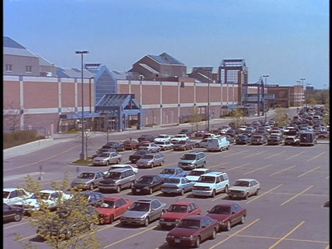Cars sit in the parking lot of a shopping mall Stock Video Footage