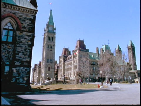A flag flies high atop a parliament building in Ottawa Stock Video Footage