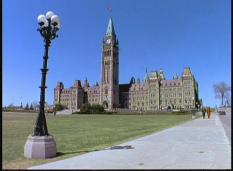 Pedestrians walk beside the Parliament of Canada in Ottawa, Ontario Footage