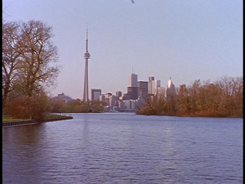 The CN tower stands in the skyline behind a lake in Canada Footage