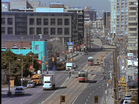 Trolleys move down a Toronto street Stock Video Footage