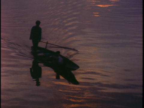 A fishermen rows a canoe in Vietnam during golden hour Footage