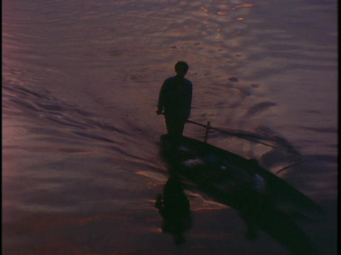 A fishermen rows a canoe in Vietnam during golden hour Stock Video Footage