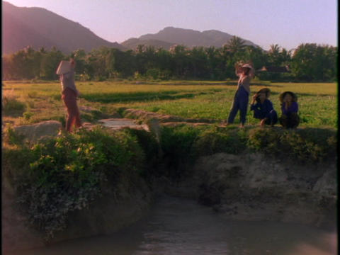 women use a rope and pail system to bail water into a field Stock Video Footage