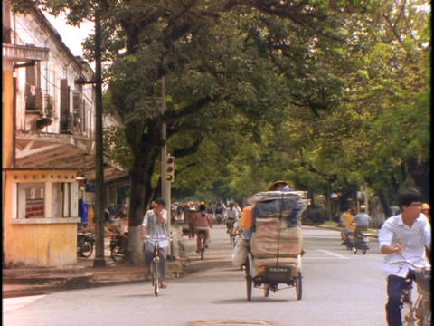 People on bicycles and scooters fill a street in Hue,... Stock Video Footage