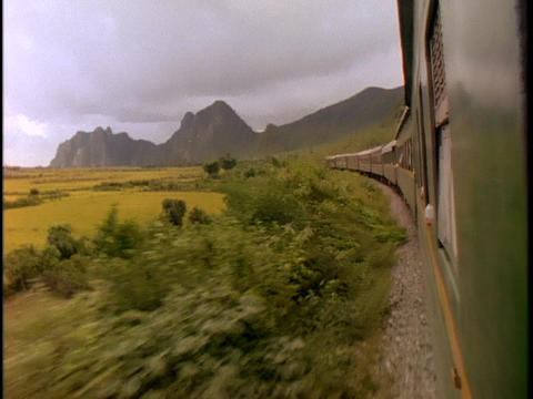 A train speeds through the Vietnamese countryside Stock Video Footage