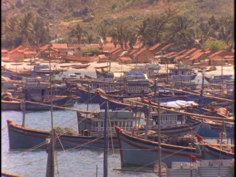 Boats sit in dock in a Vietnamese fishing village Stock Video Footage