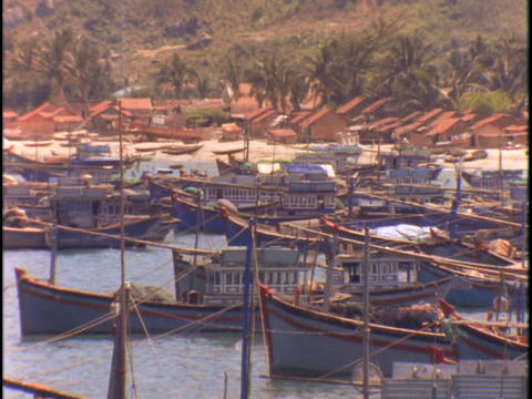 Boats sit in dock in a Vietnamese fishing village Live Action